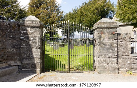 Gateway to churchyard-Churchyard in rural Wales with high stone walls and wrought iron gate leading through to old grave stones and memorials. - stock photo