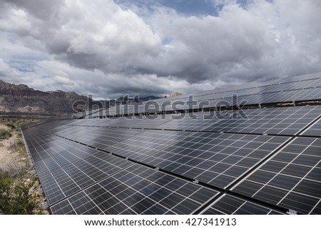 Gathering storm clouds over Mojave desert solar panels in Red Rock Canyon National Conservation Area near Las Vegas, Nevada.   - stock photo