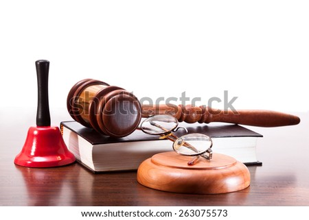 Gavel, a book of laws and glasses, a bell on the table walnut - stock photo