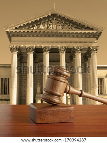 Gavel against the background of the courthouse - stock photo