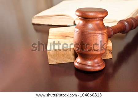 Gavel and a book lying on a table - stock photo