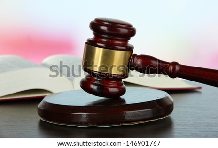 Gavel and book on table on light background - stock photo