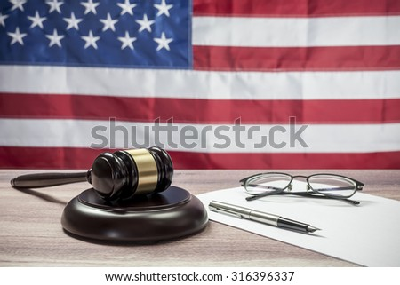 Gavel and glasses on a wooden table, American flag background - stock photo