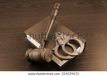 Gavel and handcuffs on legal book - stock photo