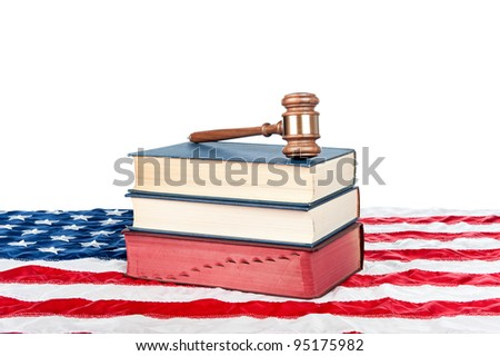 Gavel and law books resting on an American flag with a white background for placement of copy. - stock photo