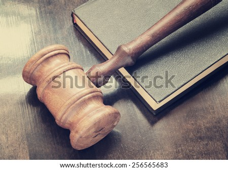 Gavel and legal book on wooden table - stock photo