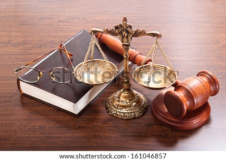 Gavel, antique scales, book and glasses on a varnished wooden table - stock photo