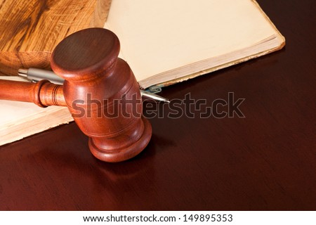 Gavel, book and pen on a lacquered table in the courtroom - stock photo