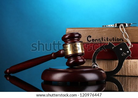 Gavel, handcuffs and books on law on blue background - stock photo
