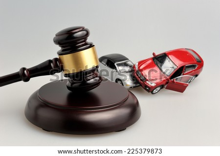 gavel judge with models of car accident on gray background - stock photo