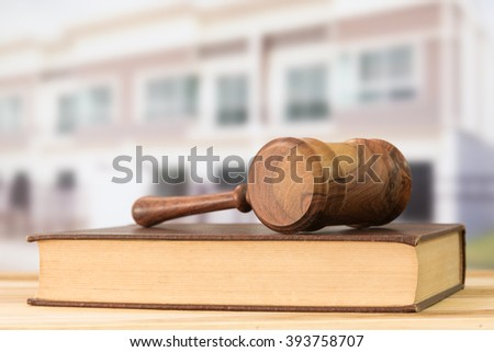 Gavel, law books with building in background. Construction law concept. - stock photo