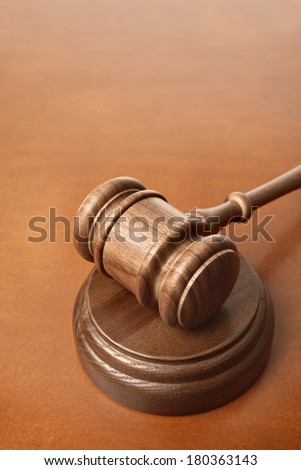 Gavel on brown leather surface - stock photo