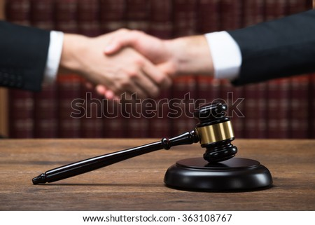 Gavel on wooden table with judge and client shaking hands in background at courtroom - stock photo