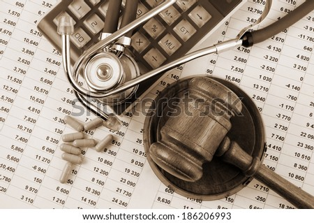 Gavel, stethoscope and pills on financial document - stock photo