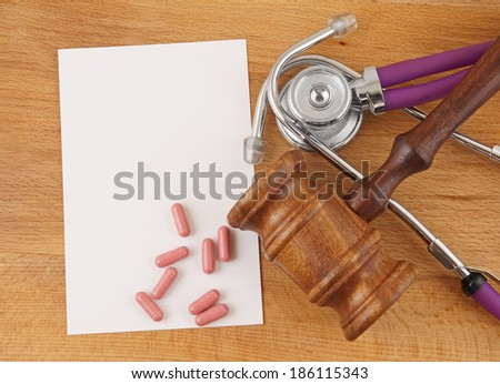 Gavel, stethoscope, pills and paper on wooden background - stock photo
