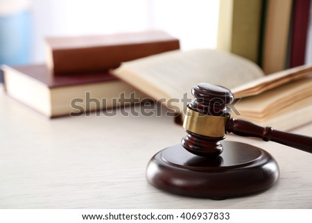 Gavel with books on wooden table closeup - stock photo
