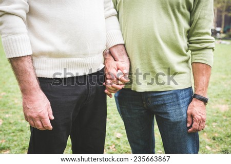 Gay Couple Holding Hands at Park - stock photo