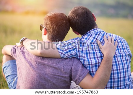 Gay couple sitting in a meadow enjoying the summer - stock photo