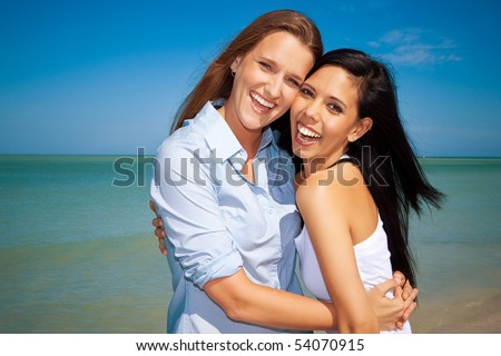 Gay couple standing at the beach, looking into camera - stock photo