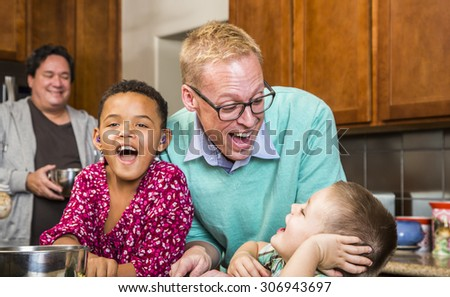 Gay couple with two adorable children laughing in kitchen - stock photo