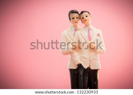 Gay groom cake toppers on pink background - stock photo