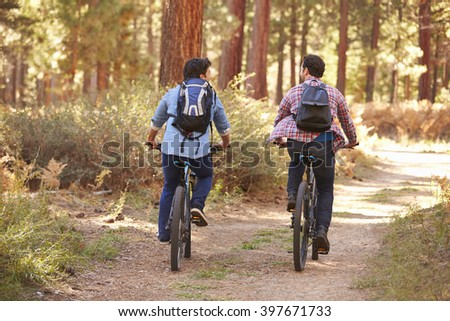 Gay Male Couple Cycling Through Fall Woodland - stock photo