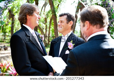 Gay male couple saying their marriage vows before a minister in lovely outdoor setting.   - stock photo