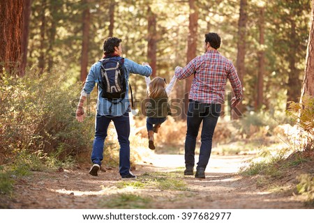 Gay Male Couple With Daughter Walking Through Fall Woodland - stock photo