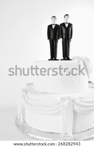 Gay marriage concept  Two men in tuxedoes wedding cake toppers copy space on white 37 US states and about 20 countries have approved same sex marriage, Ireland recently voted for equal marriage  - stock photo