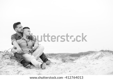 gay men lovingly embracing and cuddling on a beach - stock photo