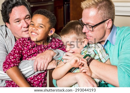 Gay parents kissing and hugging their children  - stock photo