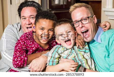 Gay parents pose with their children in the living room - stock photo