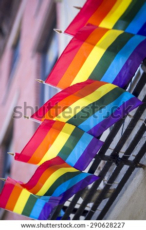 Gay pride rainbow flags hanging from traditional New York City fire escape on Christopher Street - stock photo