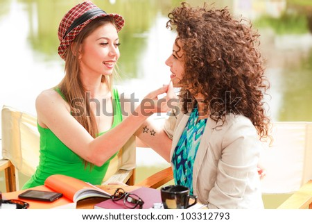 gay women couple drinking coffee and chatting on the river side terrace - stock photo