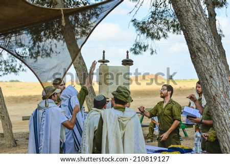 Gaza Strip/Israel -July 26th - Israeli soldiers read the scroll of Torah in July 26th 2014 in the fields around Gaza Strip during their army service. - stock photo