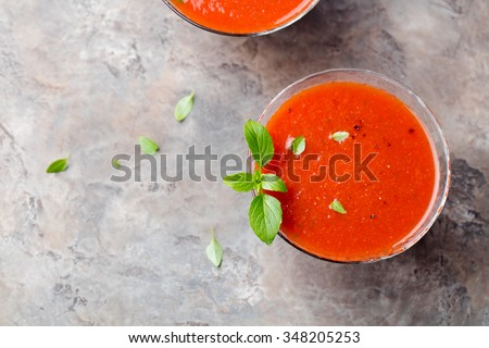 Gazpacho summer soup in glass bowl with tomato, pepper, onion, garlic, lime, olive oil, stone background - stock photo