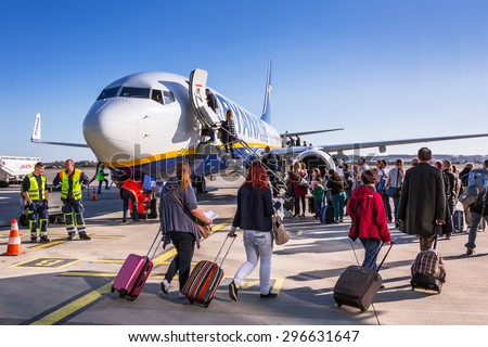 GDANSK AIRPORT, POLAND - 10 APRIL 2015: People boarding to Ryanair plane on Lech Walesa Airport in Gdansk. Ryanair operates over 300 aircraft and is the biggest low-cost airline company in Europe. - stock photo