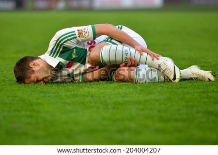 GDANSK, POLAND - APRIL 05, 2014: Injured Maciej Makuszewski lying on the grass during matc match Polish Premier League between Lechia Gdansk - KGHM Zaglebie Lubin. - stock photo