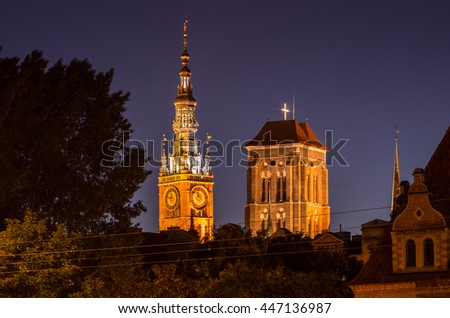 Gdansk, towers of town hall and St. Mary's Church illuminated at night - stock photo