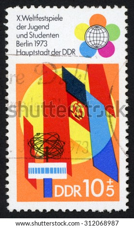 GDR - CIRCA 1973: post stamp printed in East Germany (DDR) shows emblems and flags; 10th world festival of youths and students; Berlin; Scott 1481 A458; circa 1973 - stock photo