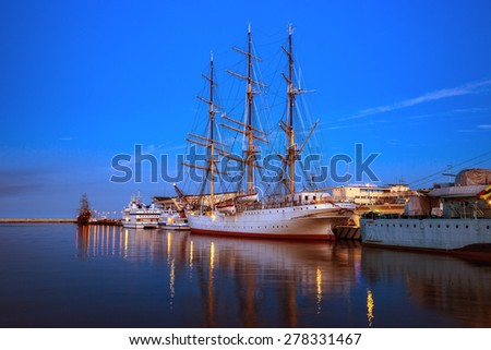 GDYNIA, POLAND - APRIL 22: Polish training tall ship Dar Pomorza at night in port on the background Maritime Academy, on April 22, 2015 in Gdynia, Poland. - stock photo
