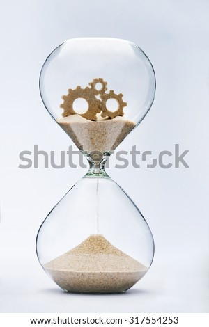 Gears of time. Connected gears flowing down in the hourglass. - stock photo