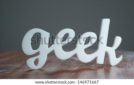 Geek Acrylic Sign on Table. - stock photo