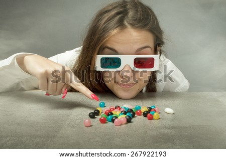 geek girl indicated candy with 3d glasses on head - stock photo