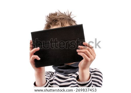 Geek kid holding a tablet device in front of his face - stock photo