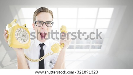 Geeky businessman shouting at retro phone against room with large window showing city - stock photo