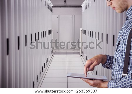 Geeky businessman using his tablet pc against data center - stock photo