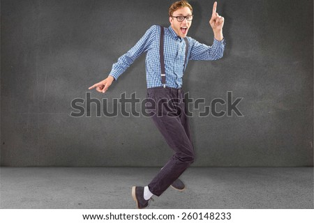 Geeky hipster dancing to vinyl against grey room - stock photo