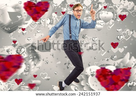 Geeky hipster dancing to vinyl against grey valentines heart pattern - stock photo