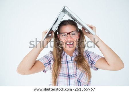 Geeky hipster holding her laptop over her head on white background - stock photo